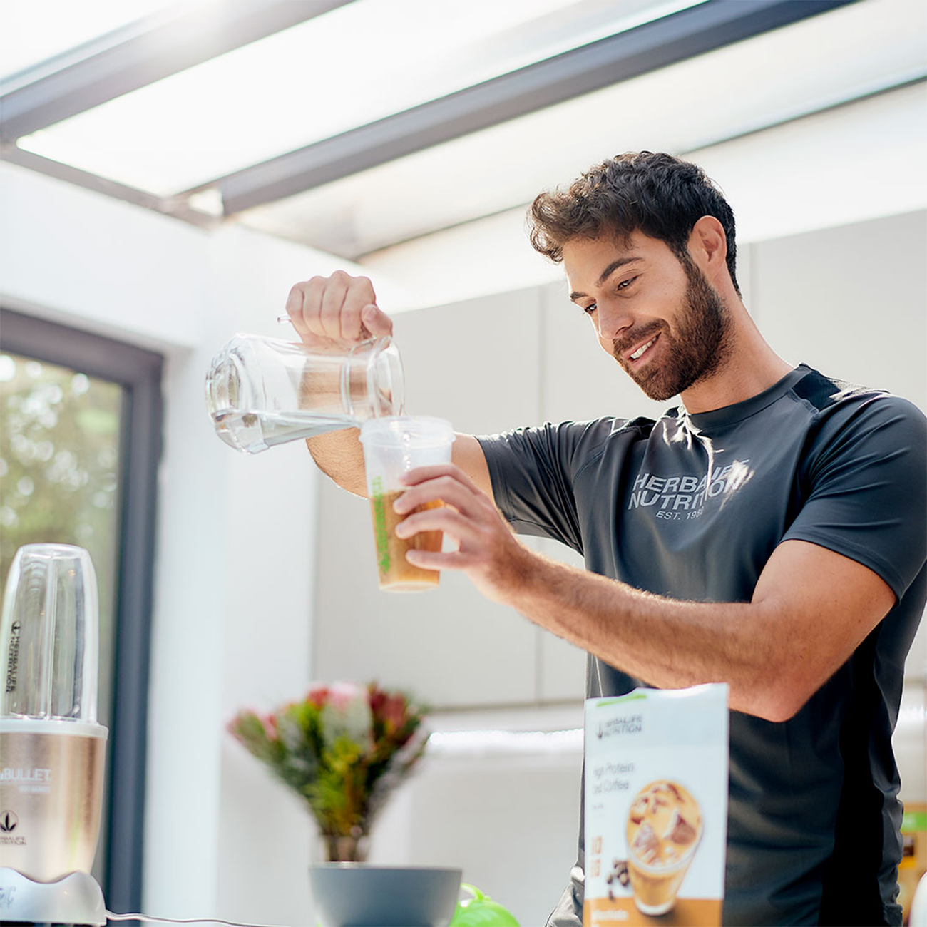 man pouring herbalife nutrition high protein iced coffee in a glass