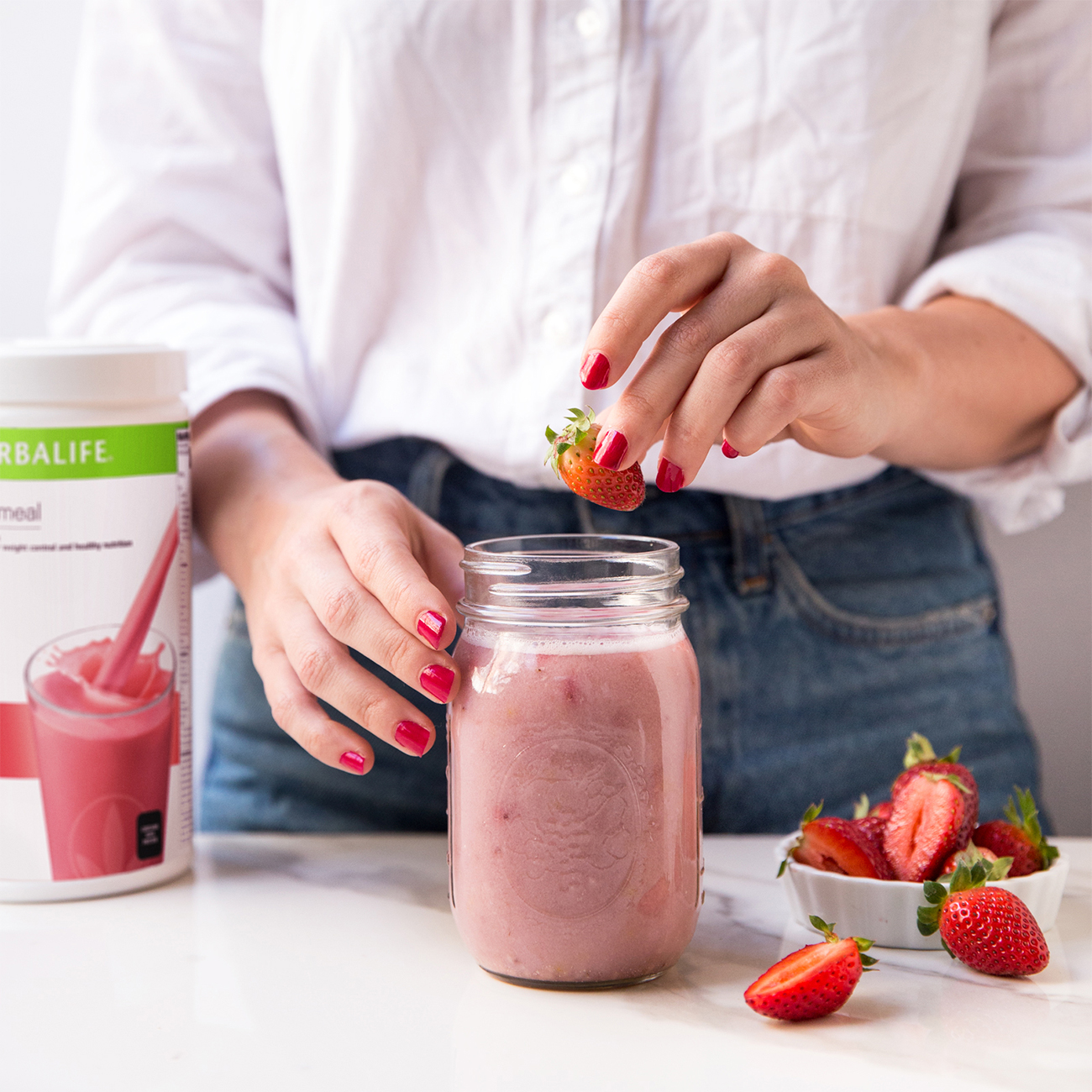 woman making herbalife nutrition strawberry shake
